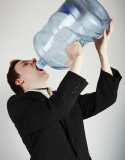 Man drinking water from huge water bottle