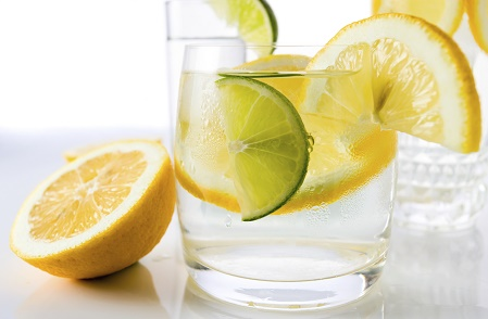 drinks with lemon and lime, shot on reflective white background.