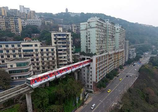 CHONGQING, CHINA - MARCH 18: A light railway train passes through a residential building on March 18, 2017 in Chongqing, China. Chongqing Rail Transit No.2 and a 19-storey residential building have been built across each other. The railway set its Liziba Station on the sixth to eighth floor in the building with noise reduction equipment. (Photo by VCG/VCG via Getty Images)