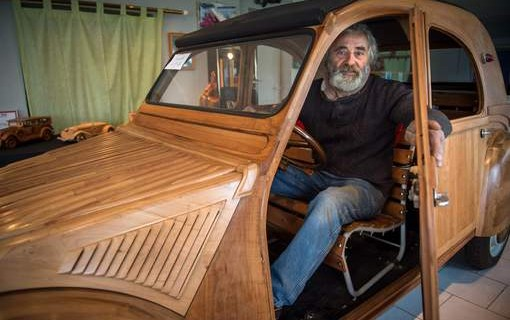 French cabinetmaker Michel Robillard poses in his handbuilt wooden 2CV Citroen Car built as an exact one/one replica on March 20, 2017, near Loches, Central France.  A retired cabinetmaker has just completed the production of a Citroen 2 CV in a Touraine fruitwood, a life-size vehicle unique in the world, equipped to take the road, which is about to pass its first technical inspection. / AFP PHOTO / GUILLAUME SOUVANT